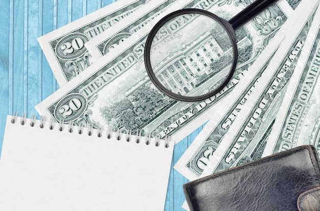 Billetes de 20 dólares estadounidenses y lupa con monedero negro y bloc de notas