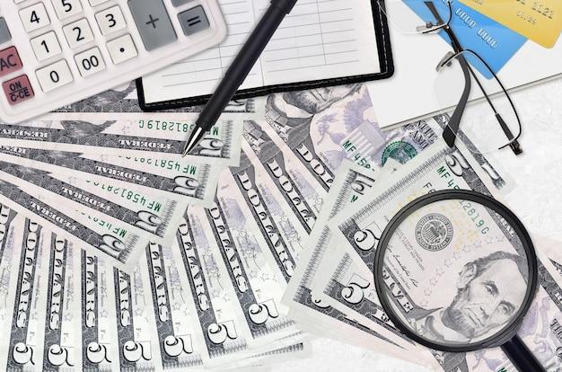 Billetes de 5 dólares estadounidenses y calculadora con gafas y bolígrafo. concepto de temporada de pago de impuestos o soluciones de inversión