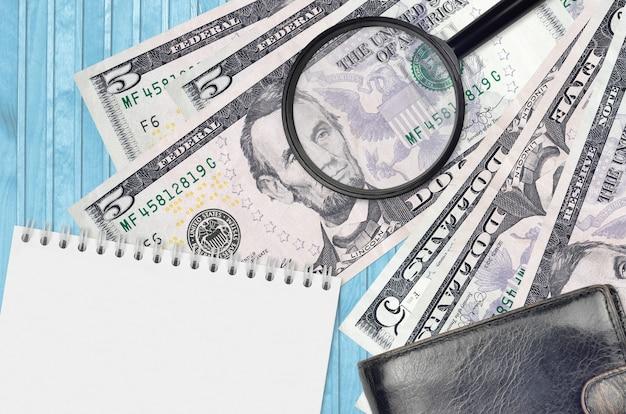 Billetes de 5 dólares estadounidenses y lupa con monedero negro y bloc de notas