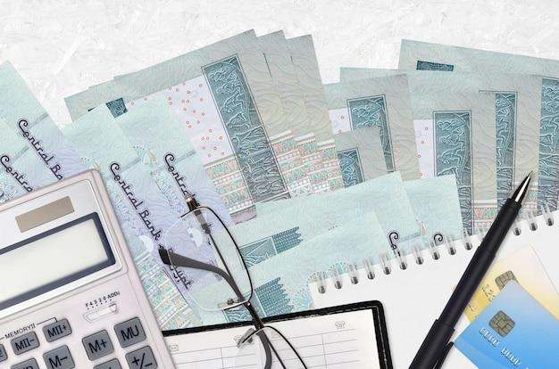 Billetes de 5 libras egipcias y calculadora con gafas y bolígrafo. concepto de temporada de pago de impuestos o soluciones de inversión. planificación financiera o papeleo contable