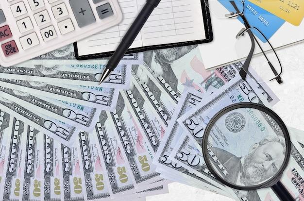 Billetes de 50 dólares estadounidenses y calculadora con gafas y bolígrafo. concepto de temporada de pago de impuestos o soluciones de inversión. buscando un trabajo con un salario alto