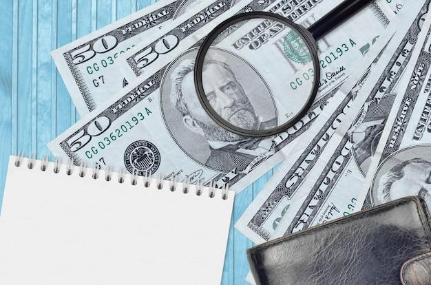 Billetes de 50 dólares estadounidenses y lupa con monedero negro y bloc de notas