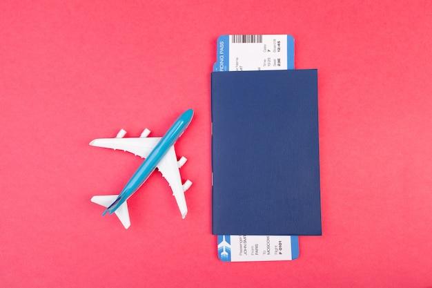 Billetes de avión y mosca en avión rosa.