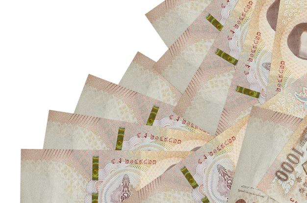 Billetes de baht tailandés sobre un fondo blanco.