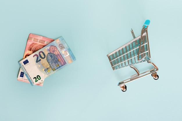 Billetes de banco y carro de compras euro en fondo azul. concepto financiero