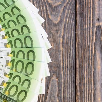 Billetes de banco euro en fan en la tabla de madera.