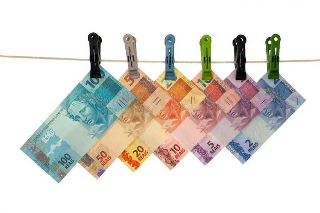 Billetes de banco reales brasileños en un tendedero - lavado de dinero - concepto de dinero sucio - aislado