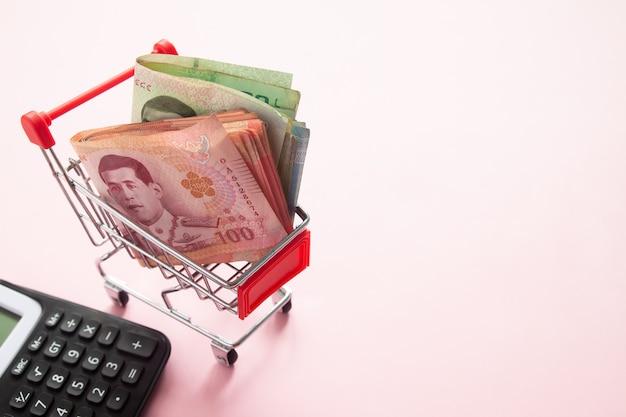 Billetes de banco tailandeses en carro de compras con la calculadora en el fondo blanco
