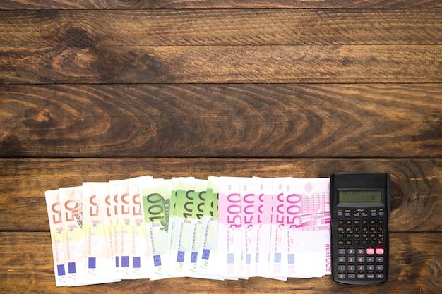 Billetes y calculadora de la vista superior en fondo de madera