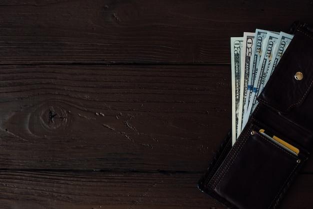 Billetes de dólar en la billetera de cuero de los hombres en la mesa de madera marrón