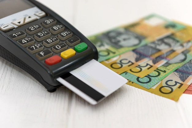 Billetes de dólar australiano con terminal y tarjeta de crédito