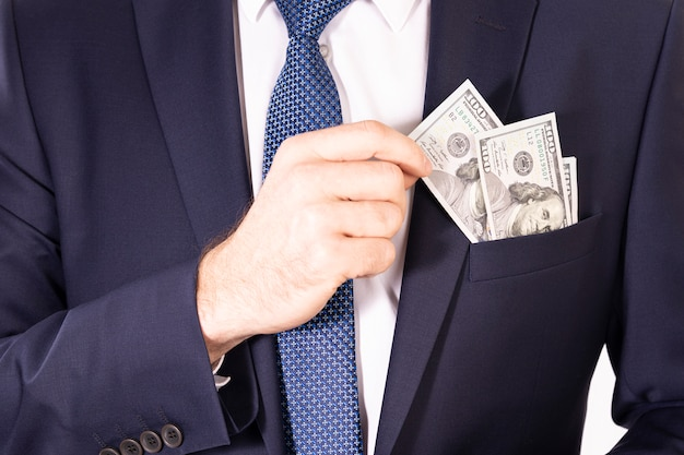 Billetes de un dólar en el bolsillo de la chaqueta de un hombre de negocios. mano saca una nota del dólar estadounidense del bolsillo de una chaqueta
