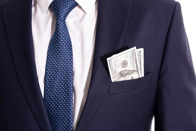 Los billetes de dólar están en el bolsillo de la chaqueta de un hombre de negocios