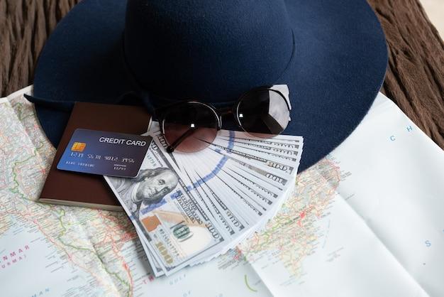 Billetes de dólar, gafas de sol, tarjeta de crédito, pasaporte y sombrero azul