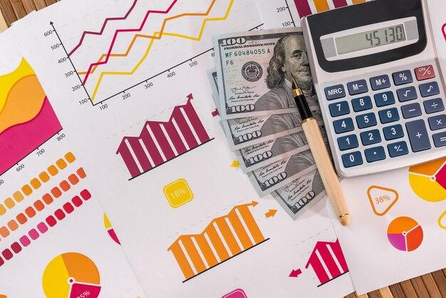 Billetes de dólar con lápiz y calculadora en gráficos de negocios
