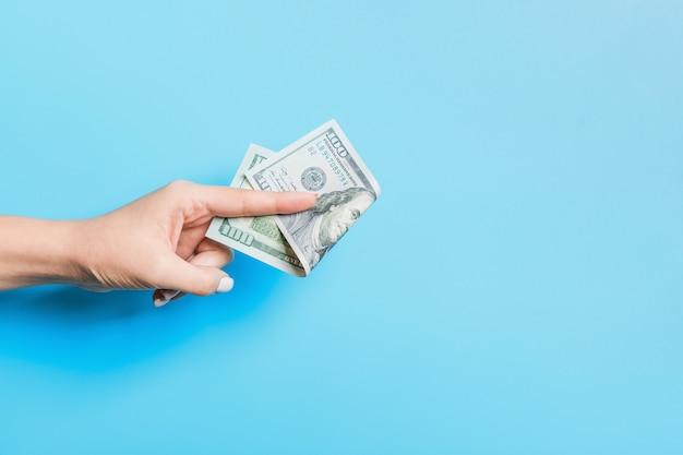 Billetes de dólar en mano femenina sobre fondo azul. concepto de negocio
