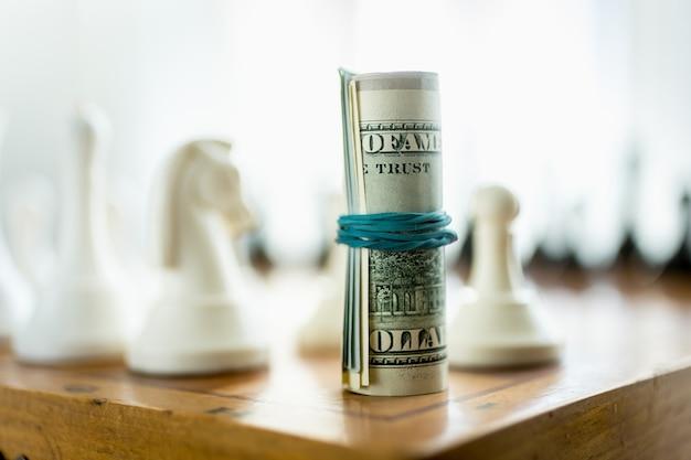 Billetes de un dólar retorcidos de pie sobre un tablero de ajedrez en lugar de la pieza de la torre
