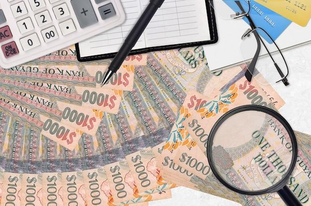 Billetes de dólares de guyana y calculadora con gafas y bolígrafo