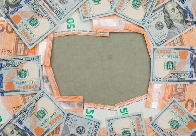 Billetes de euro y dólar financieros en mesa gris verde.
