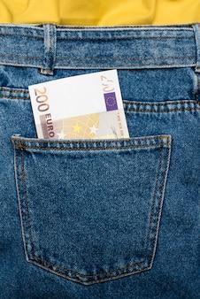 Billetes en euros en el bolsillo trasero de los jeans.