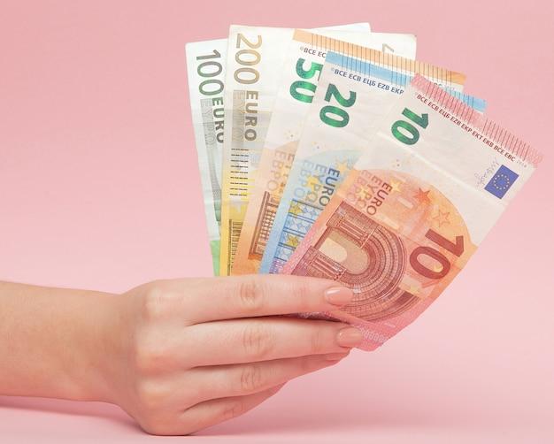 Billetes en euros dinero en manos femeninas sobre fondo rosa. concepto de negocio e instagram
