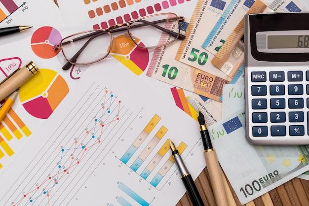 Billetes en euros en gráficos de negocios con calculadora y bolígrafo