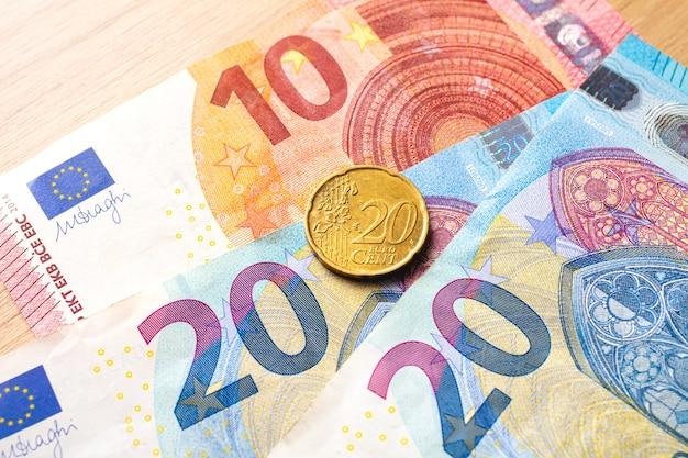 Billetes en euros con una moneda de 20 céntimos en un mueble