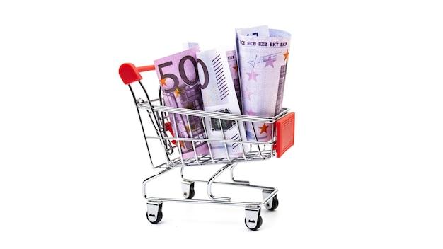 Billetes en euros en un pequeño carro sobre un fondo blanco. concepto de compra online.