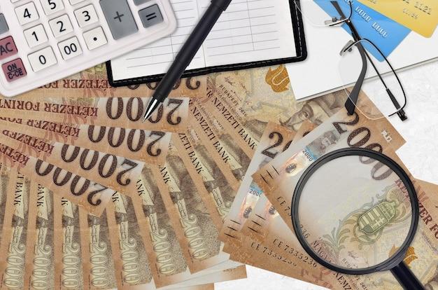 Billetes de florín húngaro y calculadora con gafas y bolígrafo