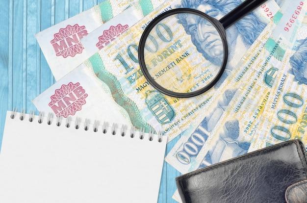 Billetes de florín húngaro y lupa con monedero negro y bloc de notas
