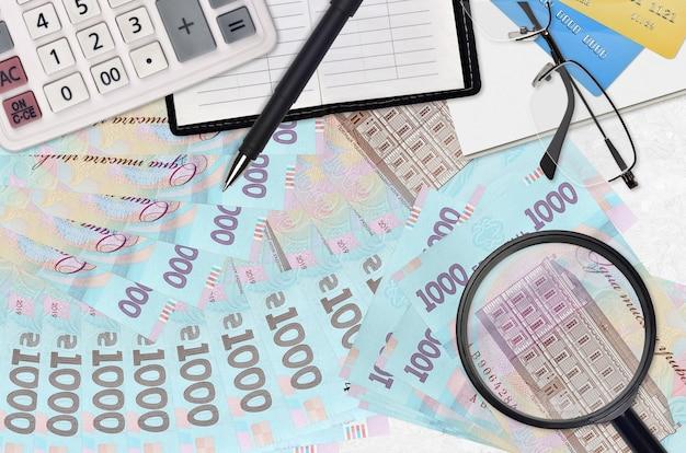 Billetes de hryvnias ucranianas y calculadora con gafas y bolígrafo