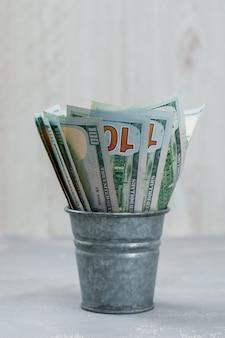 Billetes en mini cubo sobre yeso y mesa de madera
