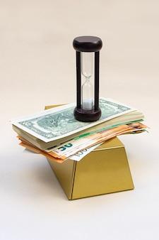 Billetes de moneda en los que hay un reloj de arena contra un brillante