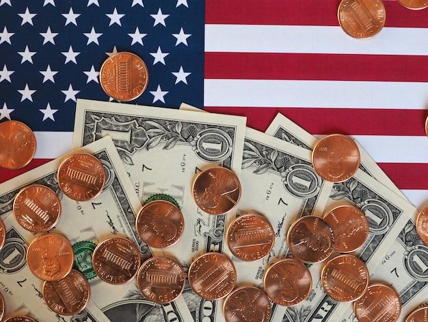 Billetes y monedas de dólar y bandera de los estados unidos