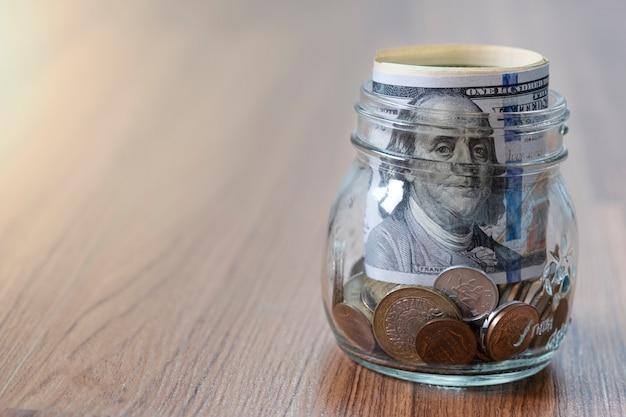 Billetes y monedas en dólares estadounidenses en frasco de vidrio