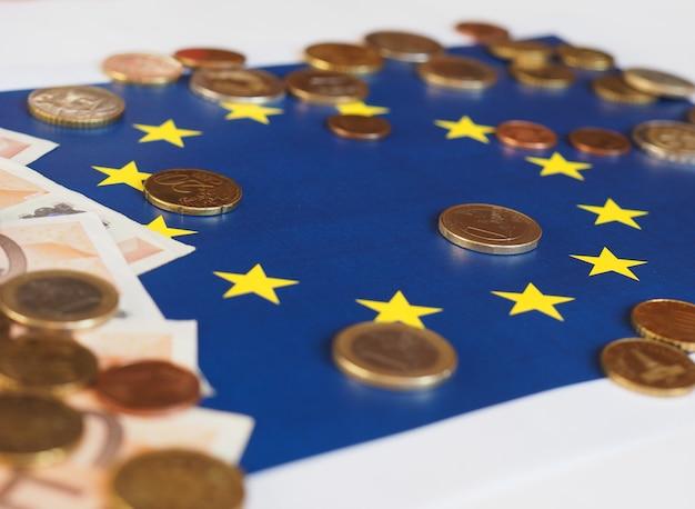 Billetes y monedas en euros (eur), moneda de la unión europea sobre la bandera de europa