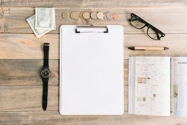 Billetes de monedas y monedas con reloj de pulsera; los anteojos; bolígrafo; diario y papel en portapapeles sobre mesa de madera