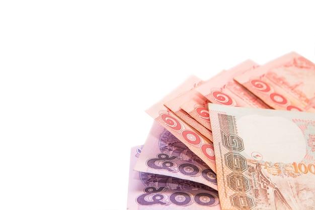 Billetes y monedas tailandesas para ahorrar sobre fondo blanco.
