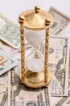 Billetes de reloj de arena y dólares estadounidenses. concepto de inversión o inflación.