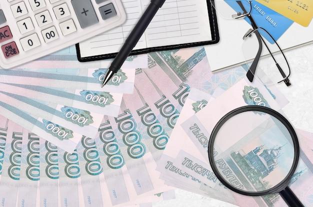 Billetes de rublos rusos y calculadora con gafas y bolígrafo