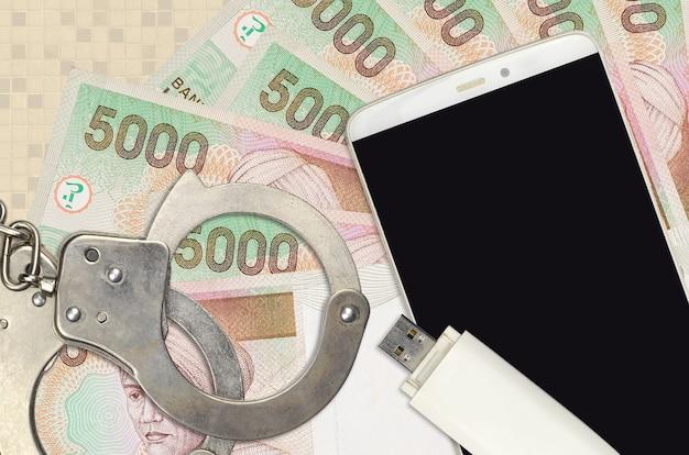 Billetes de rupia indonesia y teléfono inteligente con esposas de policía
