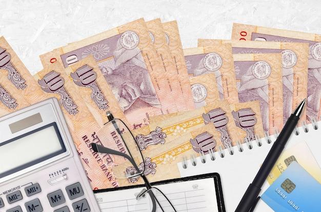 Billetes de rupias indias y calculadora con gafas y bolígrafo