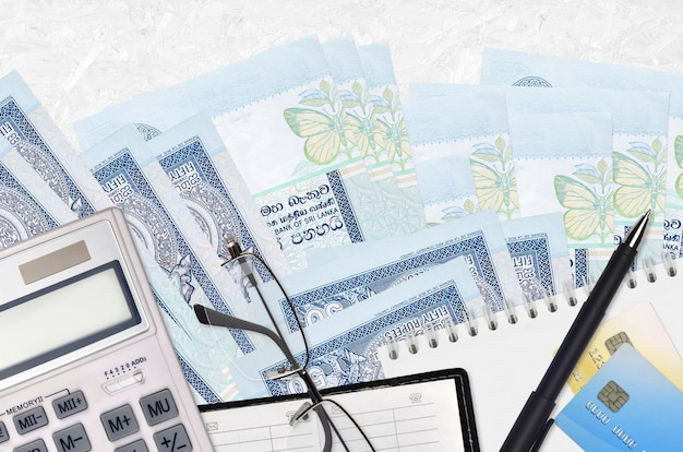 Billetes de rupias de sri lanka y calculadora con gafas y bolígrafo