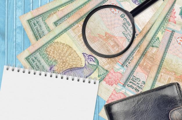 Billetes de rupias de sri lanka y lupa con monedero negro y bloc de notas
