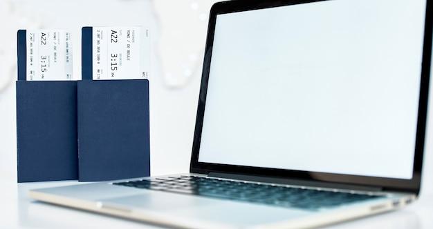 Billetes de viaje con pasaporte cerca de la computadora portátil.