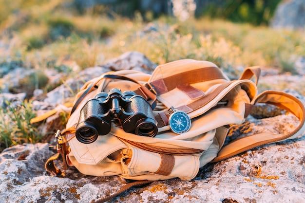 Binocular, brújula y bolso en la roca