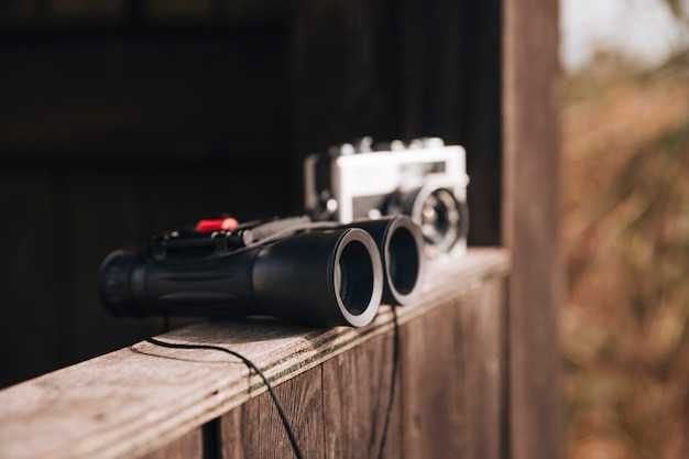 Binoculares y cámara fotográfica en una repisa de madera.