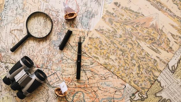 Binoculares y lupa en mapas retro