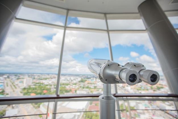 Binoculares en la parte superior del edificio para el telescopio turístico mira la ciudad con vista