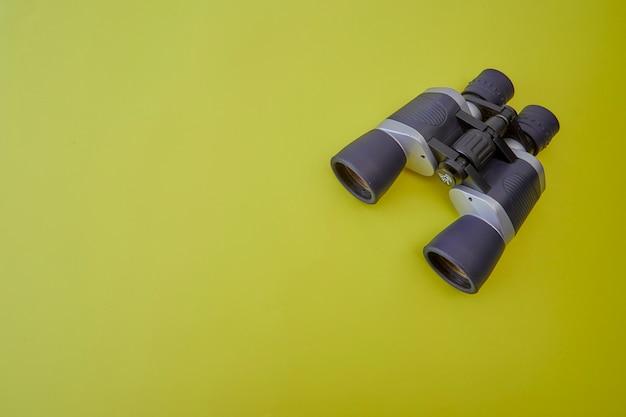 Binoculares de plata y gris sobre fondo amarillo.